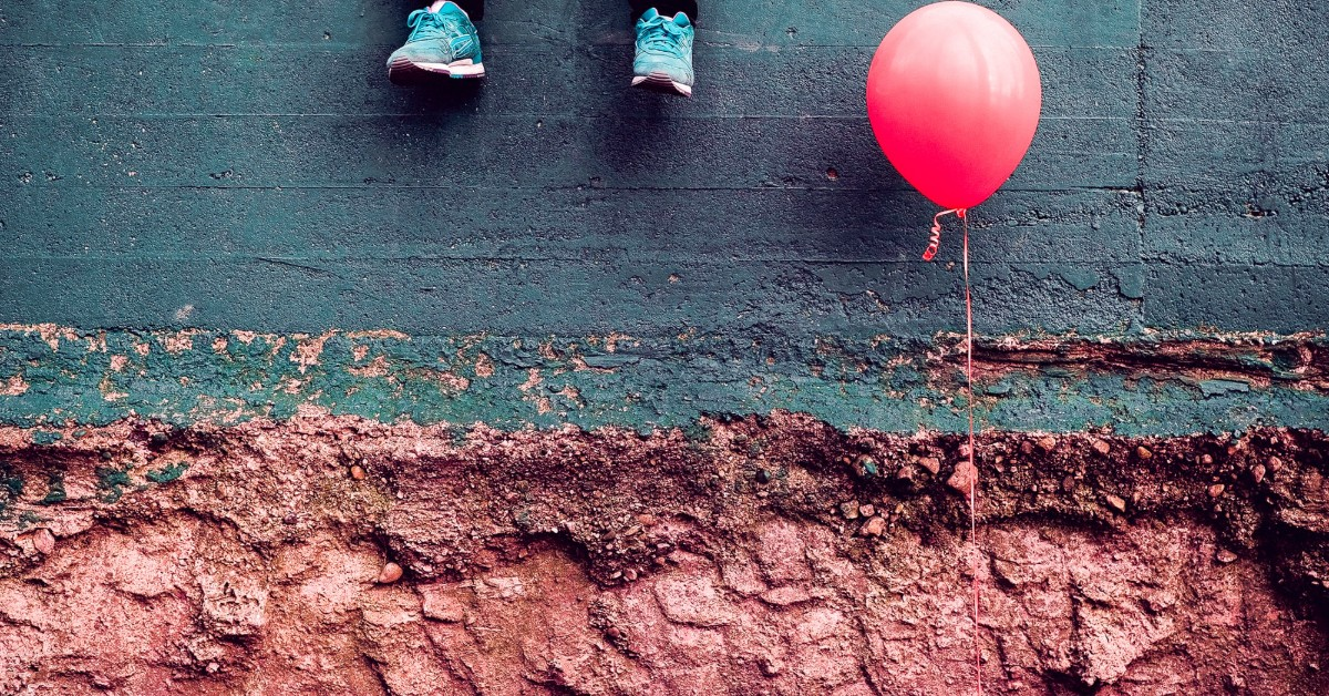 A child's blue sneakers and a pink balloon