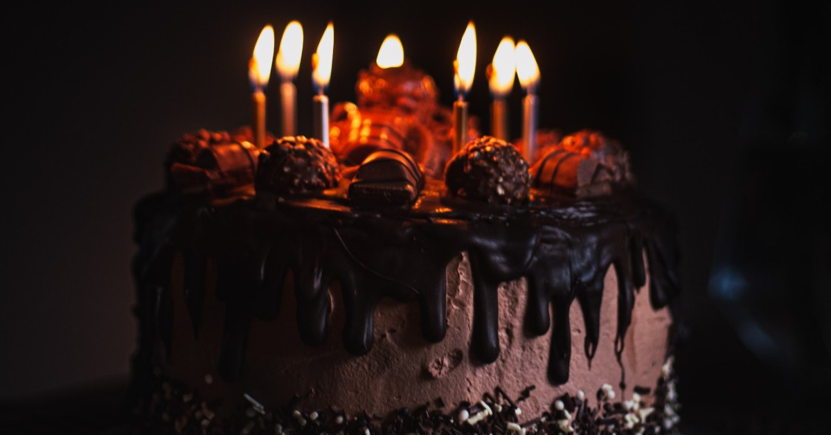 Chocolate birthday cake with lighted candles