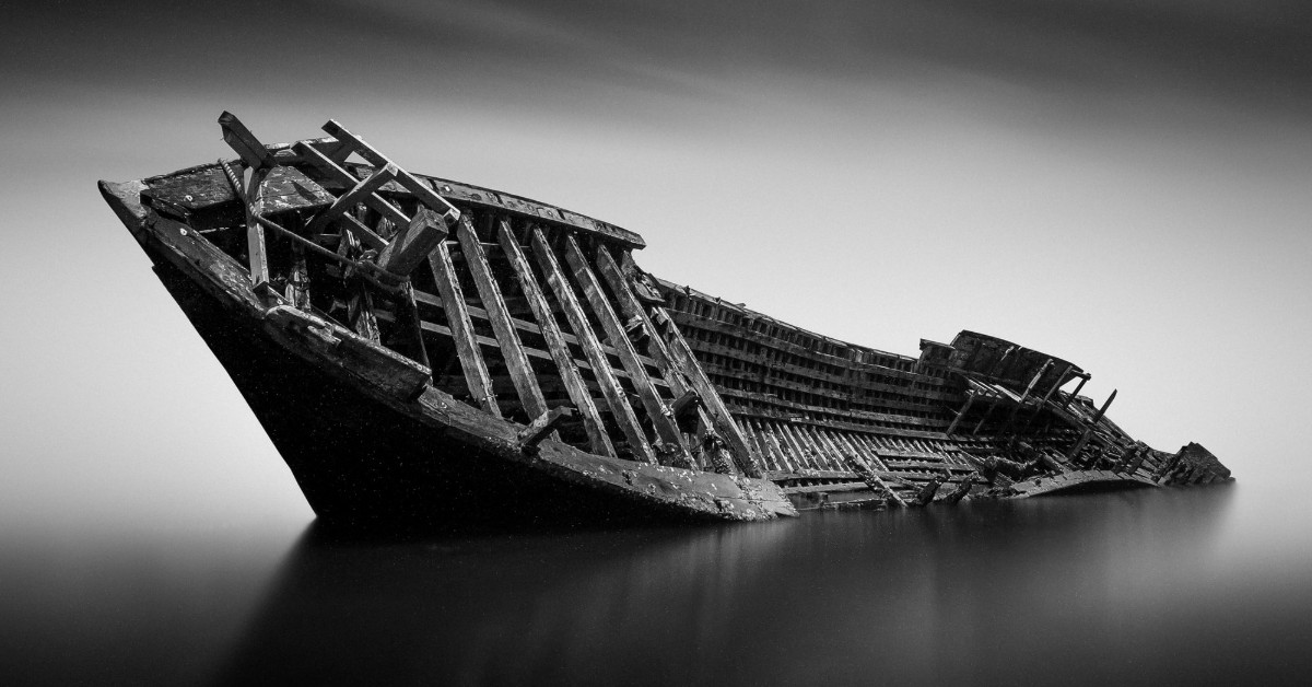 Black and white image of a wrecked ship in water