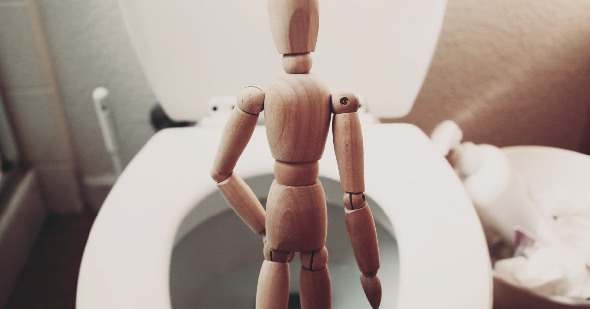A small wooden figurine standing in front of a flush in peeing posture