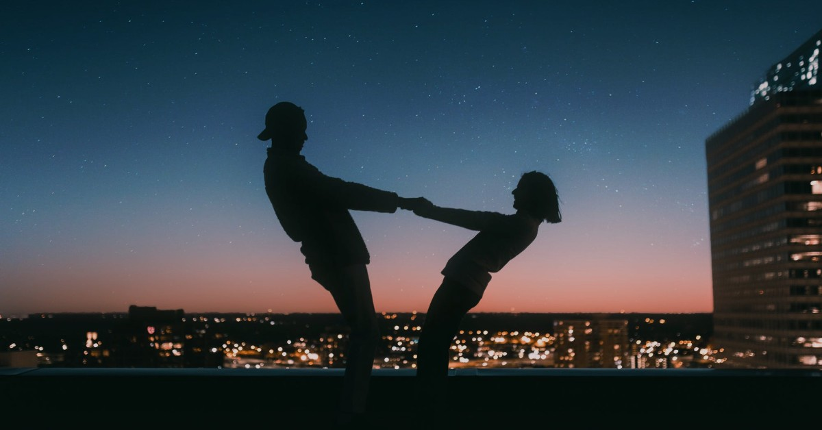 At dusk with the city skyline behind them, the silhouettes of a couple holding hands and leaning backwards