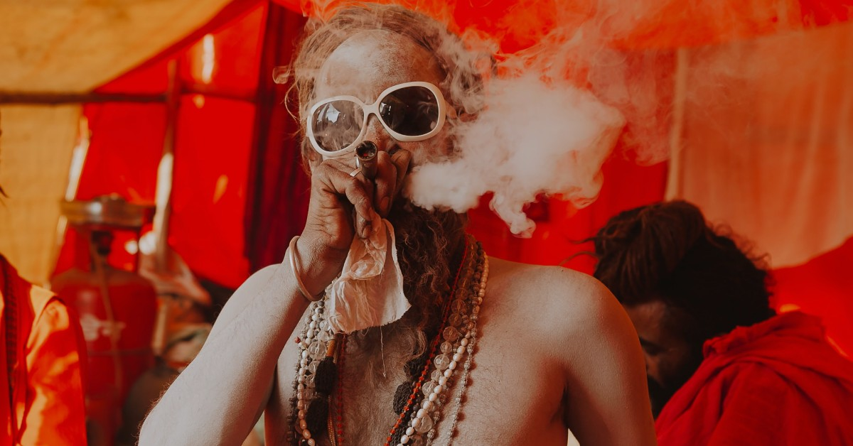 A swami wearing sunglasses and beaded necklaces smoking an opium pipe