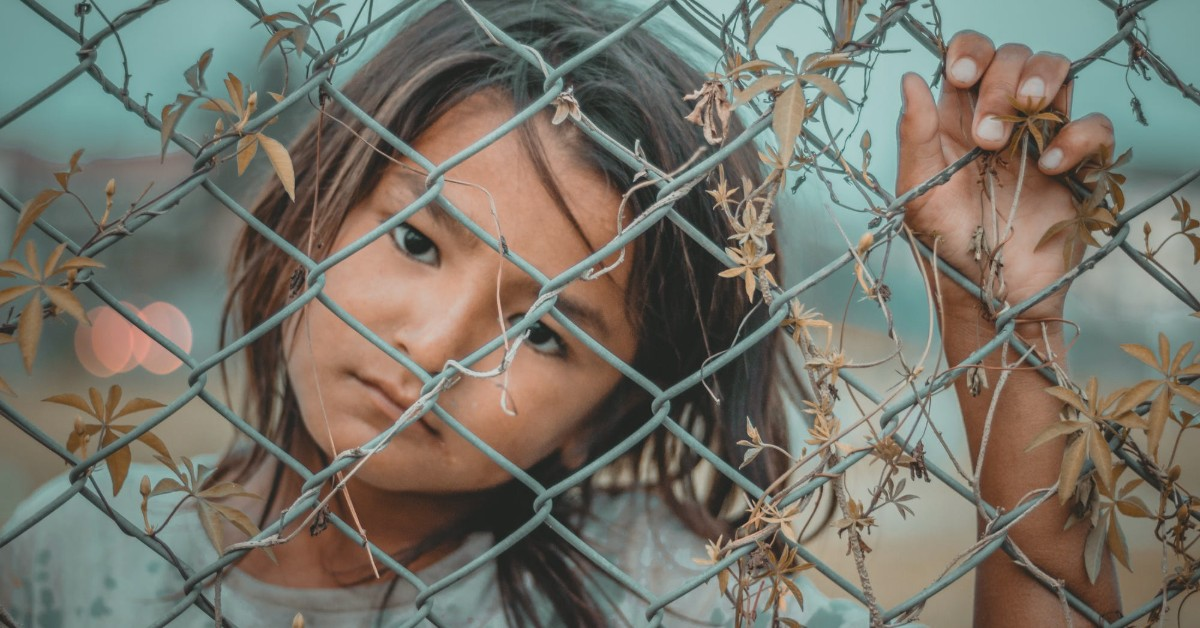 A young girl in dirty clothes standing and staring from behind a wired fence