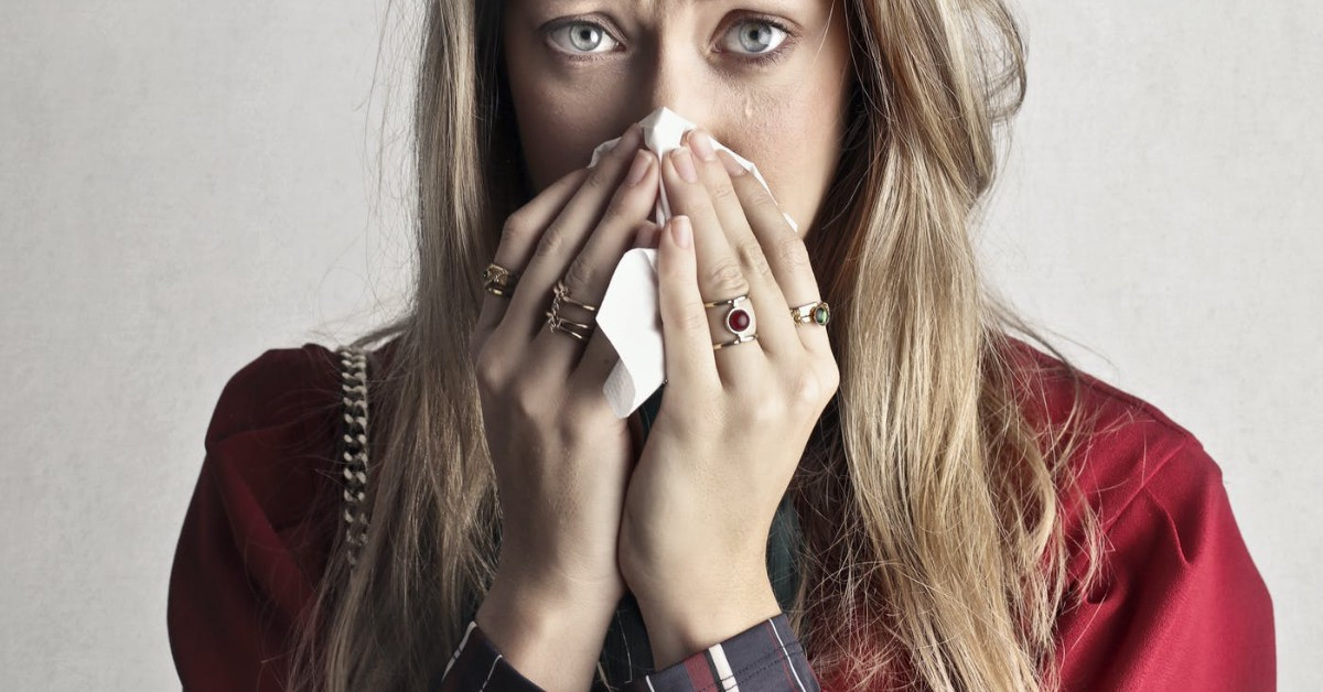 A white woman who is crying and blowing her nose into a tissue