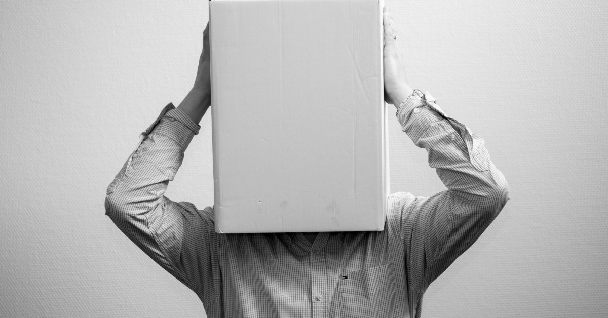 A black and white image of a man in a shirt holding a box that he has placed over his face and head