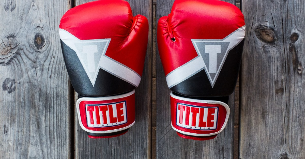 A pair of black and red boxing gloves lying on a wooden table
