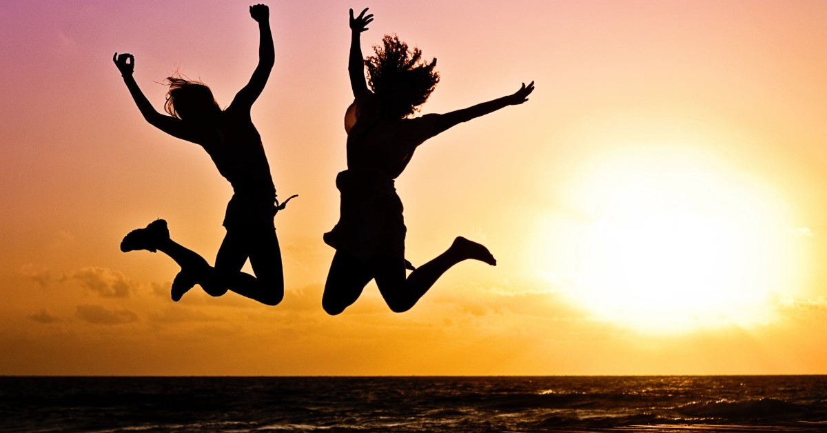 The silhouette of two young girls jumping up with the setting sun behind them on a beach