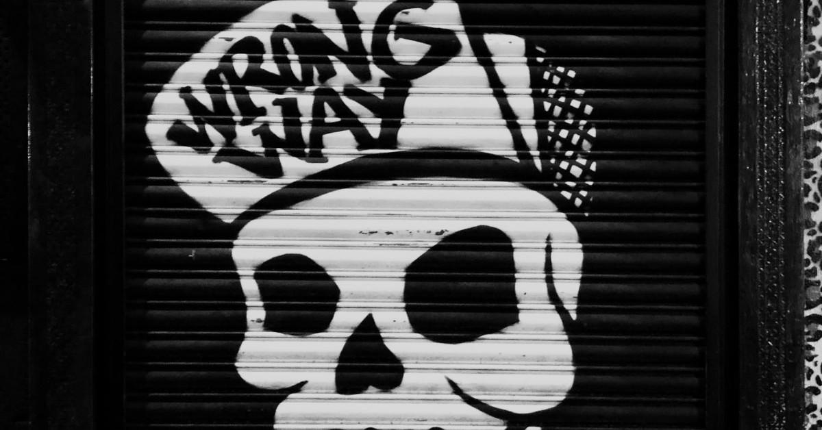 A graffiti of a skull wearing a cap that says 'Wrong Way'.