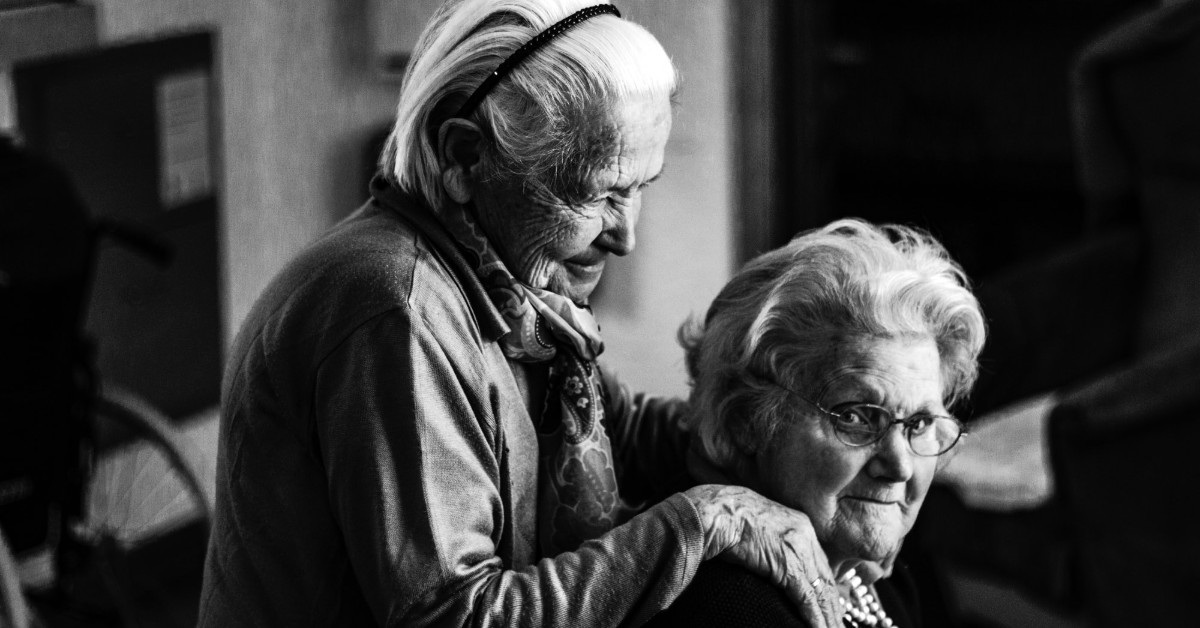 One old lady standing behind another old lady with her hands on the woman's shoulders