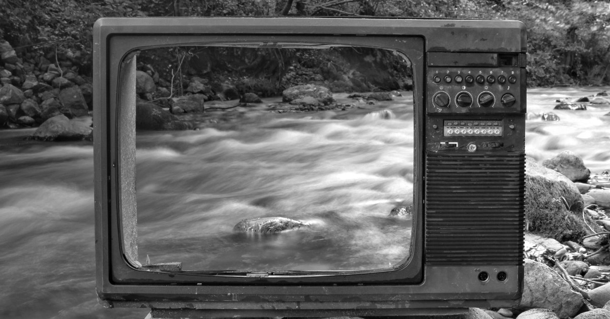 A black and white image of an old TV with no screen and behind which is a flowing river