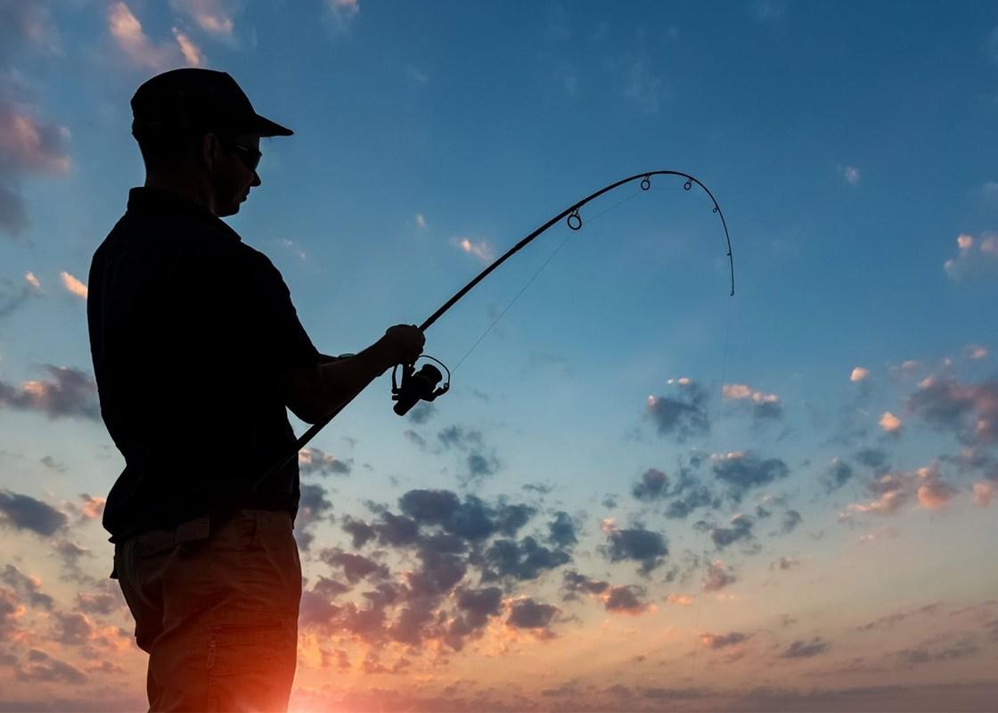 Man fishing at sunset