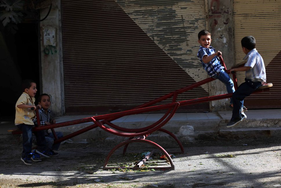 TOPSHOT - Syrian boys play on a see-saw in the Syrian rebel-held town of Arbin, in the eastern Ghouta region on the outskirts of the capital Damascus, as they celebrate the Muslim Eid al-Adha holiday on September 13, 2016, the day after an internally backed ceasefire for Syria came into effect as part of a hard-fought deal to bring an end to the war between rebels and regime fighters.  / AFP / AMER ALMOHIBANY        (Photo credit should read AMER ALMOHIBANY/AFP/Getty Images)