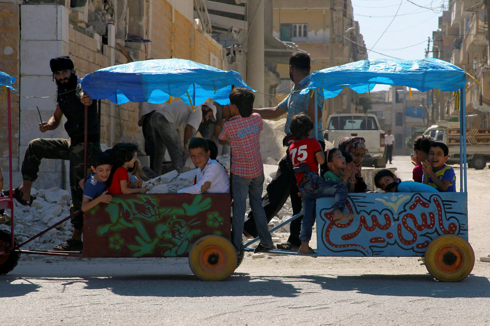 Children ride a cart on the 3rd day of Eid al-Adha in the rebel controlled city of Idlib, Syria September 14, 2016. REUTERS/Ammar Abdullah
