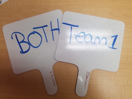 "Two whiteboard paddles with ""team 1"" and ""Both"" written on them."
