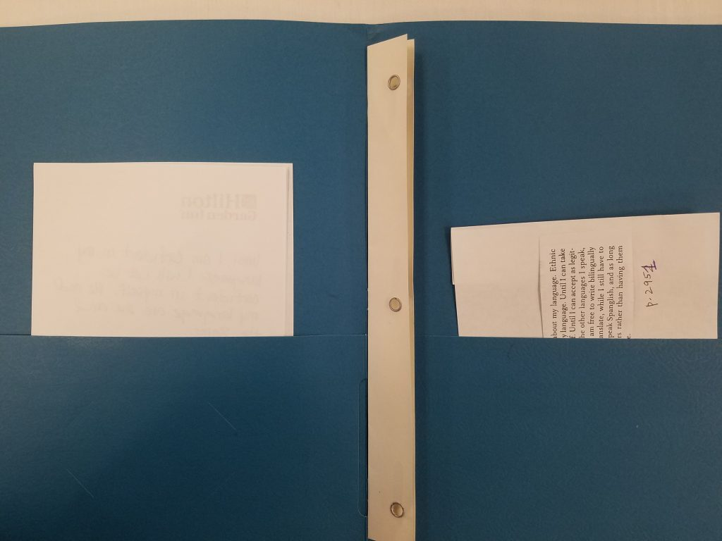 Blue folder with paragraph in one side and a blank paper in the other.