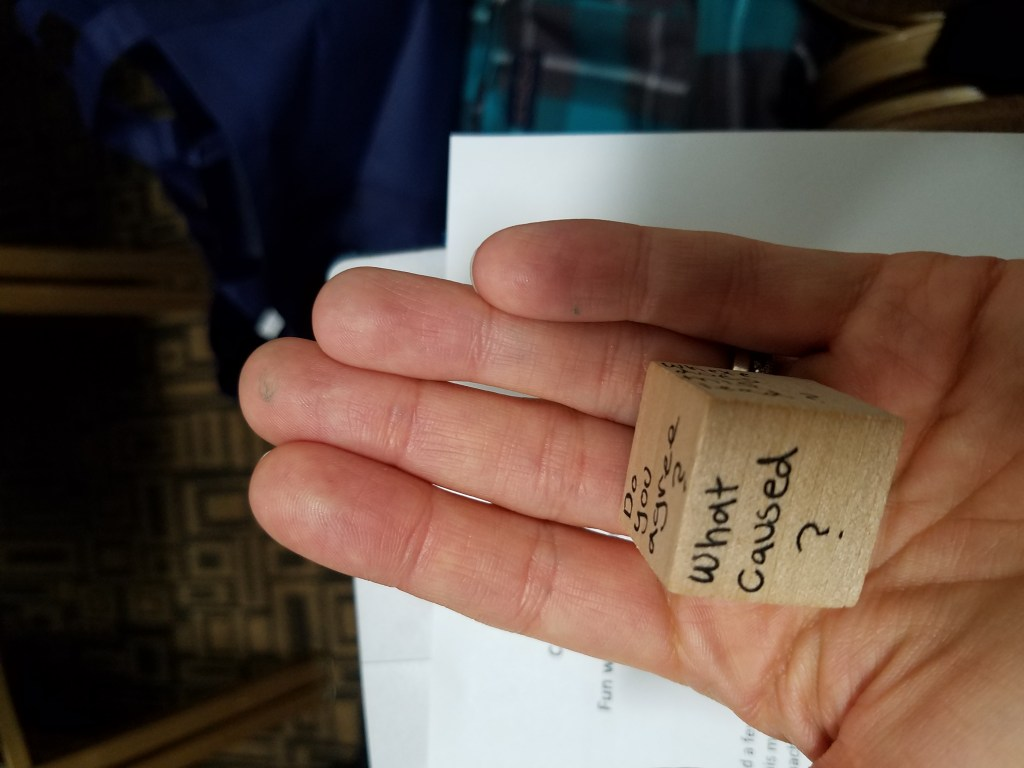 Hand holding wooden dice with a question on it.
