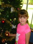 Violet holds the bauble bearing her name. Each child has a bauble on my tree.