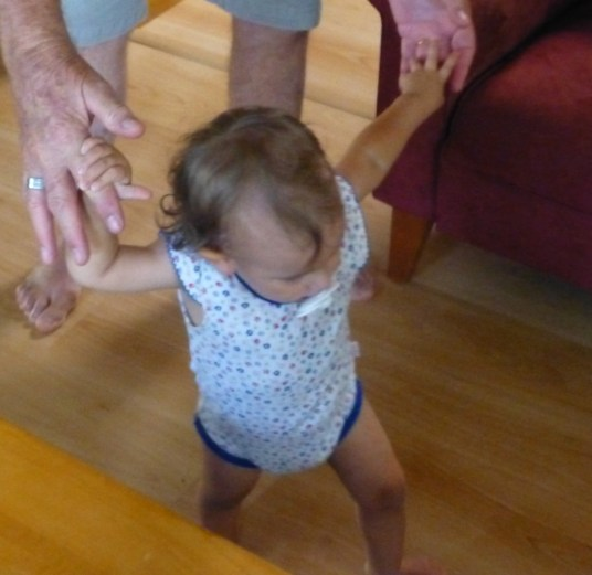 Madeleine hanging on to Grandpa's hand as she tries to walk alone for a second time.
