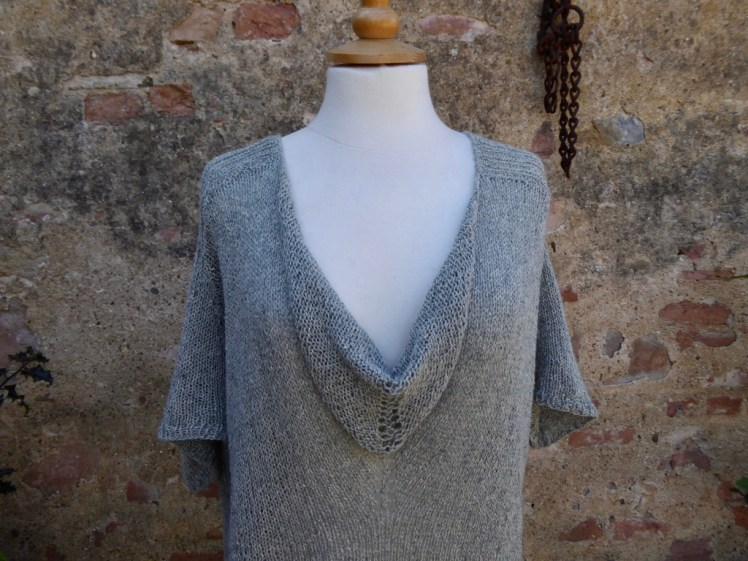 A picture of the top front of the Cowl neckline top showing the short handkerchief sleeves, photographed against a red brick and render wall.