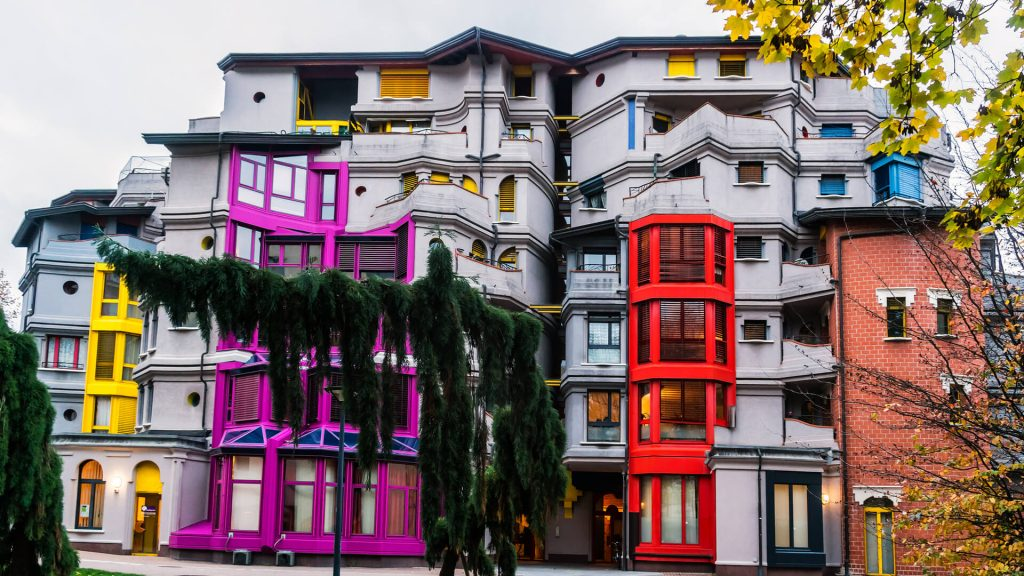 Building in Quartier des Grottes with yellow, pink and red window frames