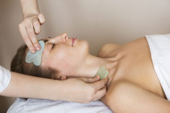 84917142 - young woman have face guasha treatment at asian beauty clinic