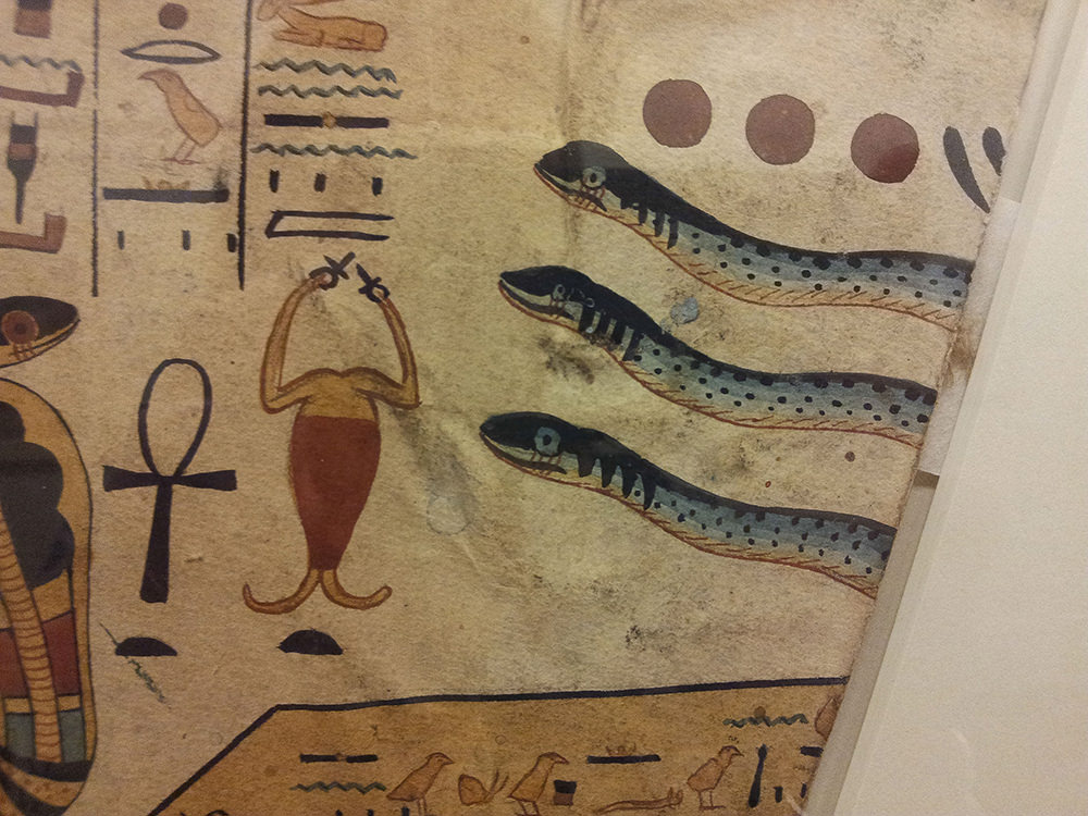 A close up of the beginning of the fourth hour showing the front of three snake painted blue, with black spots and stripes, with a red and yellow scorpion in front of them