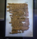 A papyrus with some damage to it, particularly down the left-hand side. The text is written in black ink and the papyrus is in a black frame with a white backing