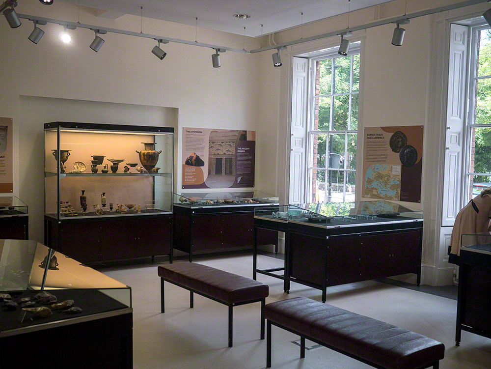 A view of one of the galleries with display cases around the edge, tall windows on the back wall and two benches in the centre of the room
