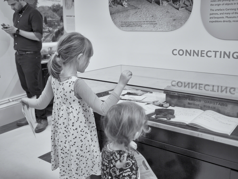 Two young girls in a museum gallery, looking for items on a piece of paper