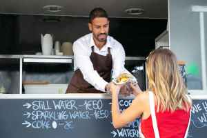 female buying tasty burger in food truck