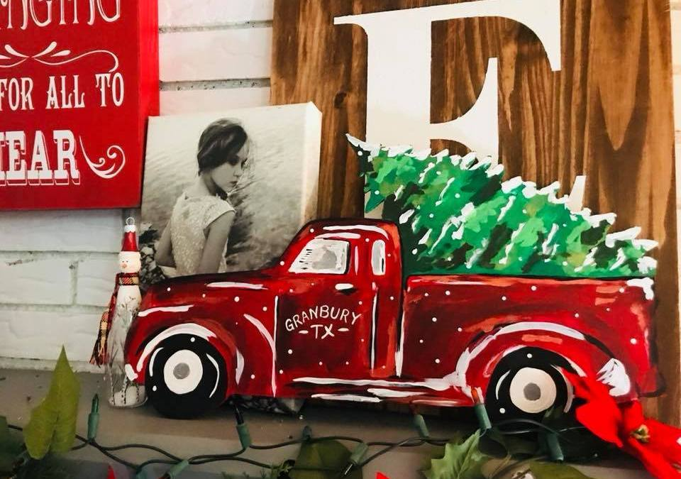 Painted truck with a Christmas tree covered in snow