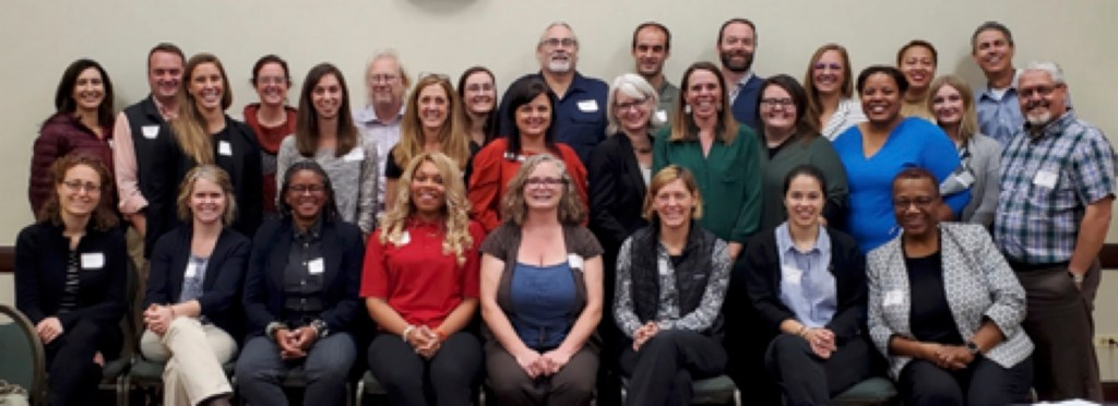 Group photo of about 30 adults who worked together on the core curriculum project.