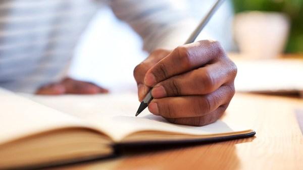 man writing in book