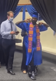 Corey Borner walks across the stage with high tech assistance to accept his college diploma at UNT