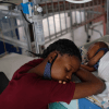 A woman sleeping beside a child in a pediatric center