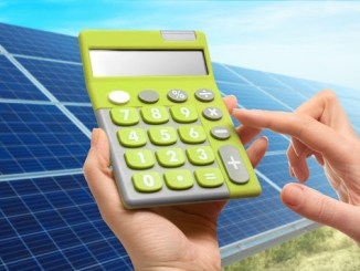 a calculator being used with solar panels in the background