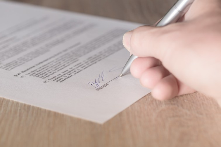 White hand signing the bottom of a contract with a silver pen on a wooden table.