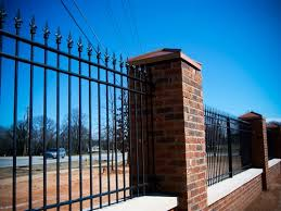 Wrought iron fence with brick pillars in between segments, cars driving on a road, bare trees, and a bright blue sky in the background.
