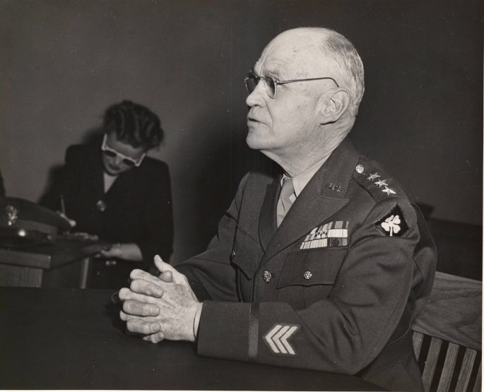 black and white photo showing Lt. General DeWitt with a stenographer in the background