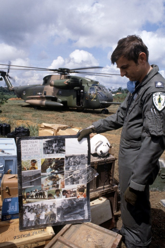 Image of Lieutenant Colonel (LTC) Leonard Morrisey, an HH-53 Jolly Green Giant helicopter pilot from the 55th Aerospace Rescue and Recovery Squadron, examines a poster found at the compound as the remains of the victims of the Jonestown tragedy are loaded aboard the helicopter (NAID 6413446)
