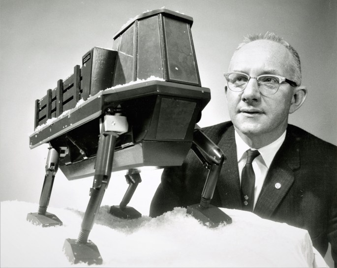 photograph of man, Ralph S. Mosher, looking at a quadruped model.