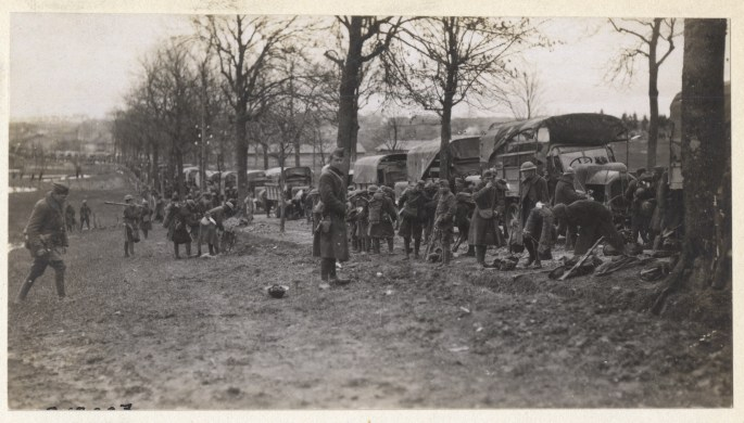 troops lined up along trucks at the edge of a field
