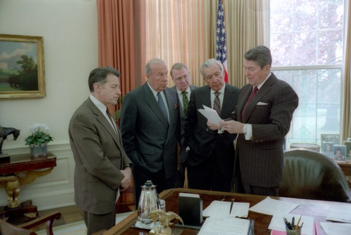 Reagan and 3 other men standing at the corner of the resolute desk in the oval office looking at a paper he holds in his hands