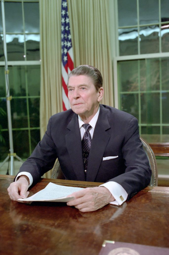 Reagan seated at the resolute desk looking into a camera that is out of shot