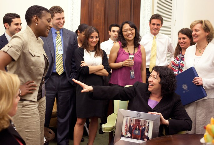 Sotomayor seated and laughing with people standing around her