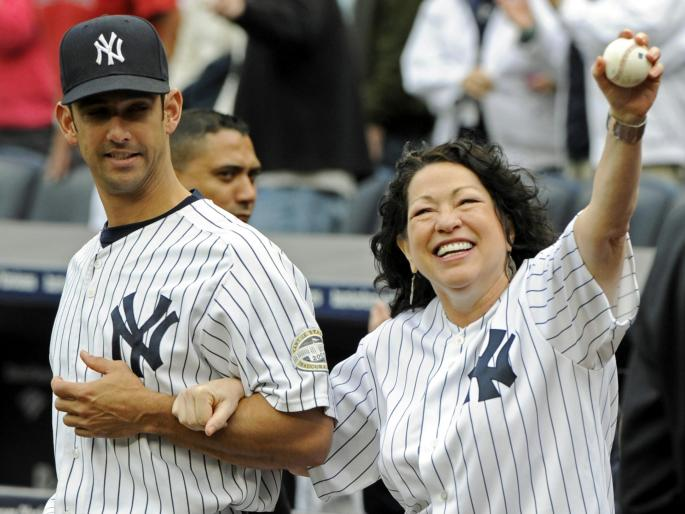 Sotomayor in Yankees jersey holding a baseball high and smiling