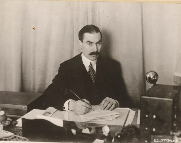 mustached man in dark suit sitting at desk with pen to paper