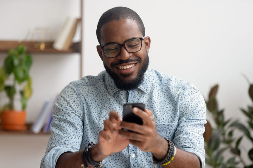 man happily looking at mobile