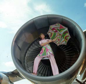 Image 2 (above). Braniff hostess wearing a floral Pucci uniform and umbrella standing in the front part of a jet engine. Braniff Airways Collection, History of Aviation Collection, Eugene McDermott Library, The University of Texas at Dallas.