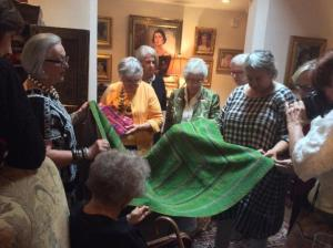 Participants having a feel of one of the textiles in Suzanne Sug's (extreme left) collection
